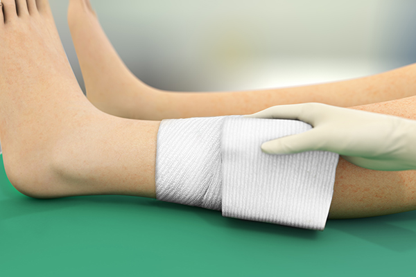 An illustrated leg and a hand holding a dressing around its ankle.