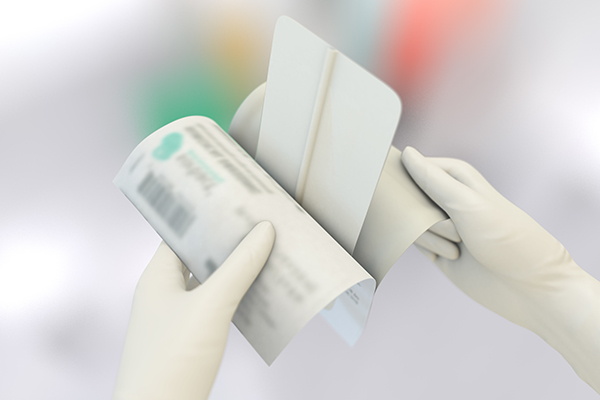 Two hands remove sorbact surgical dressing from pouch